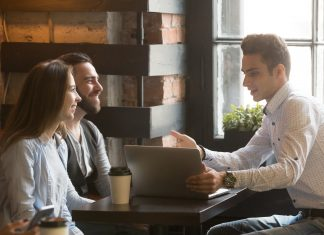 Insurance broker or salesman making offer to couple in cafe