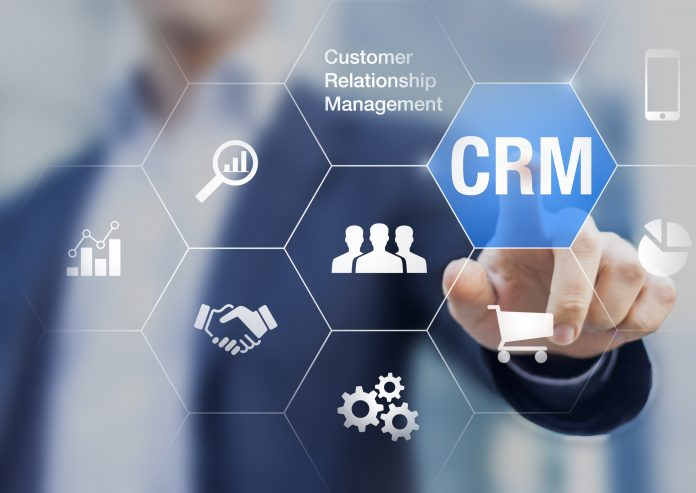Customer relationship management concept with businessman touching button in background