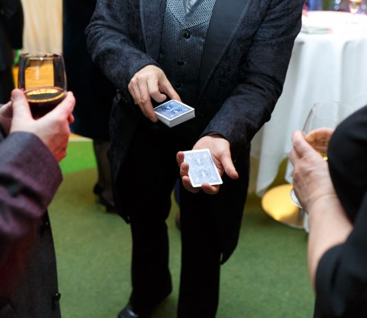 The magician shows a card trick for two spectators.