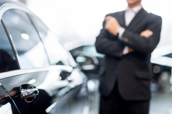Choosing a car at dealership. Thoughtful grey hair man in formalwear leaning at the car and looking away